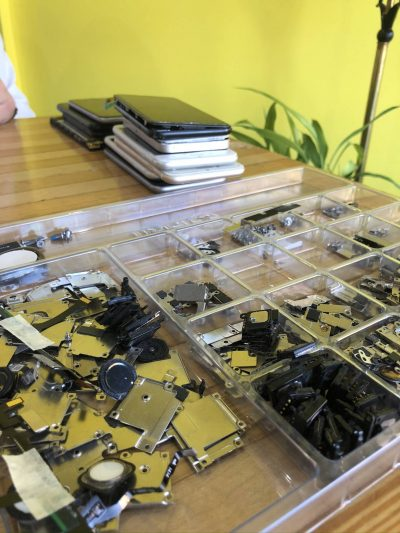 Pieces of electronic devices sorted into pieces on a tabletop ready for electronic recycling at The Lab